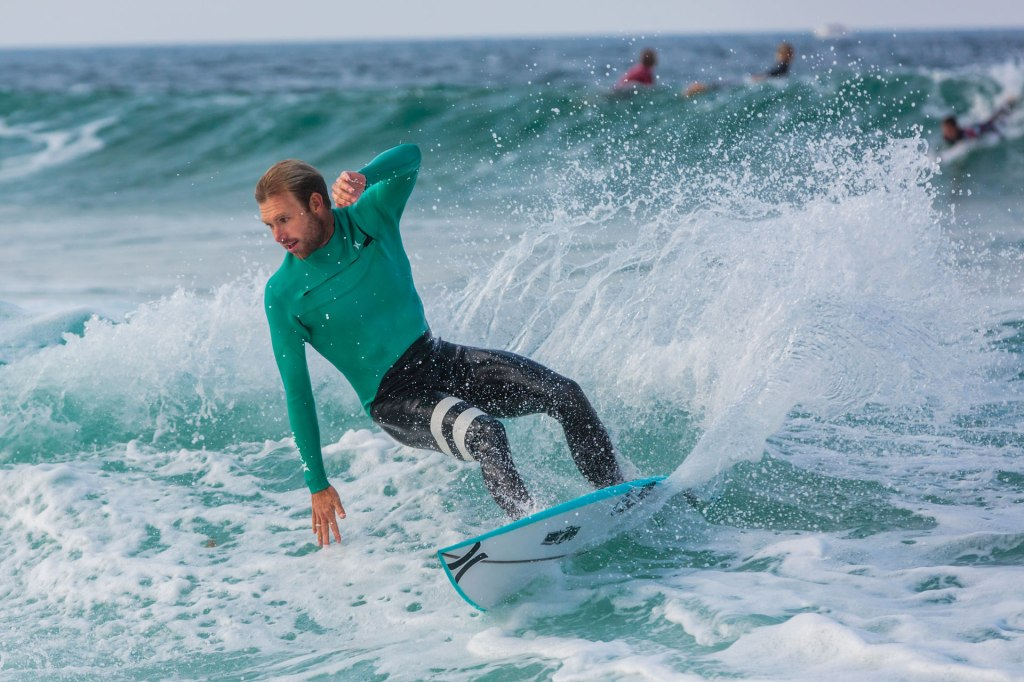 Surfer, Adrian 'Ace' Buchan, carving his surfboard on blue water in France.